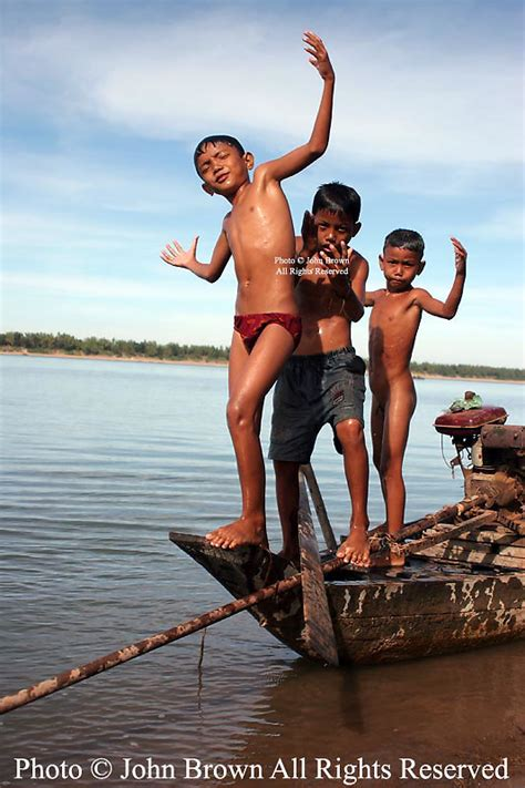 Three boys use an old fishing boat as a diving platform in